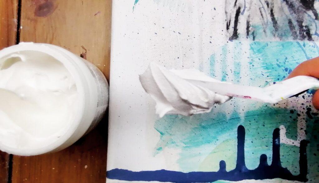 spatule qui applique de la pâte à craqueler sur une toile